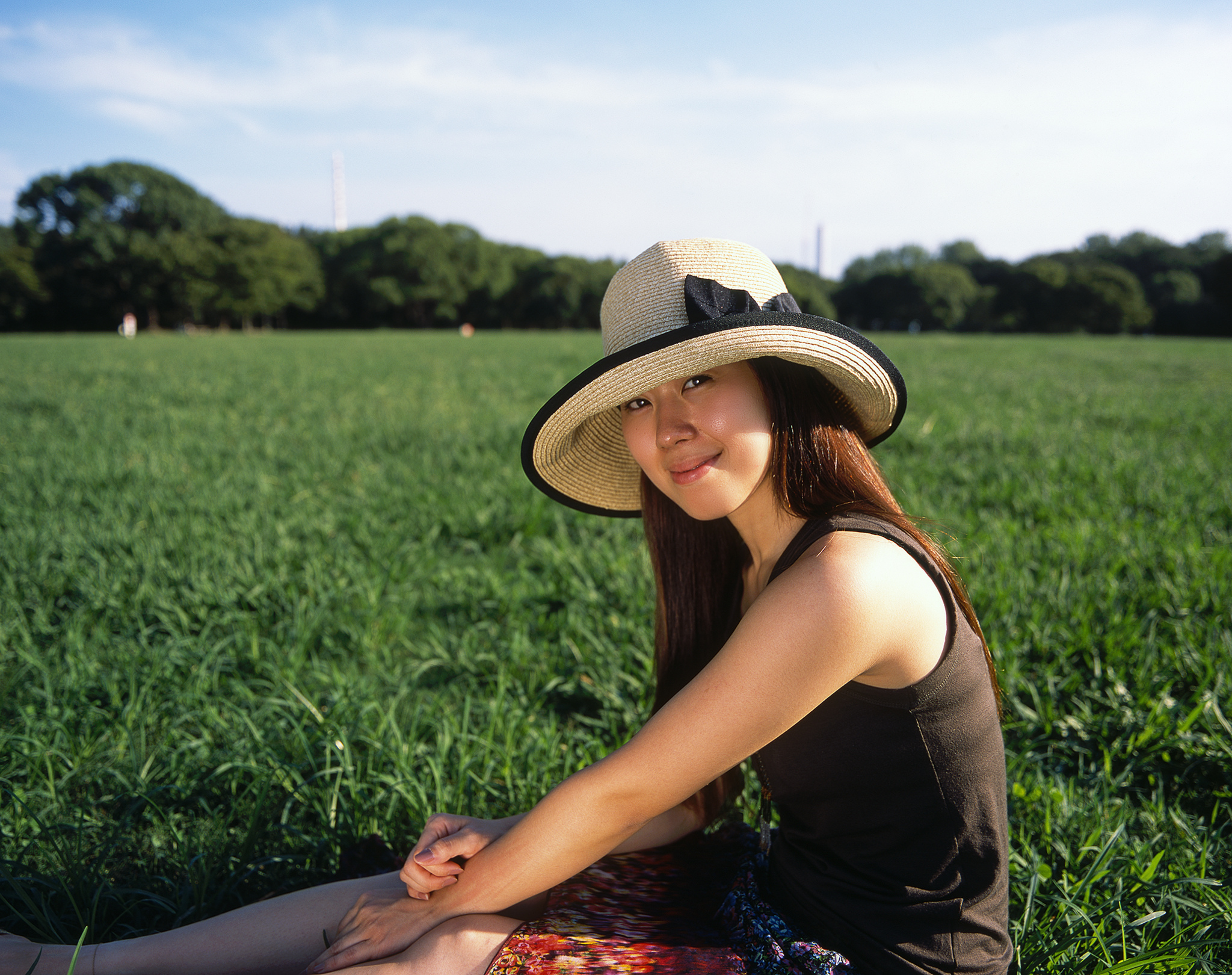 Yuka sitting in a grassy field on a clear day
