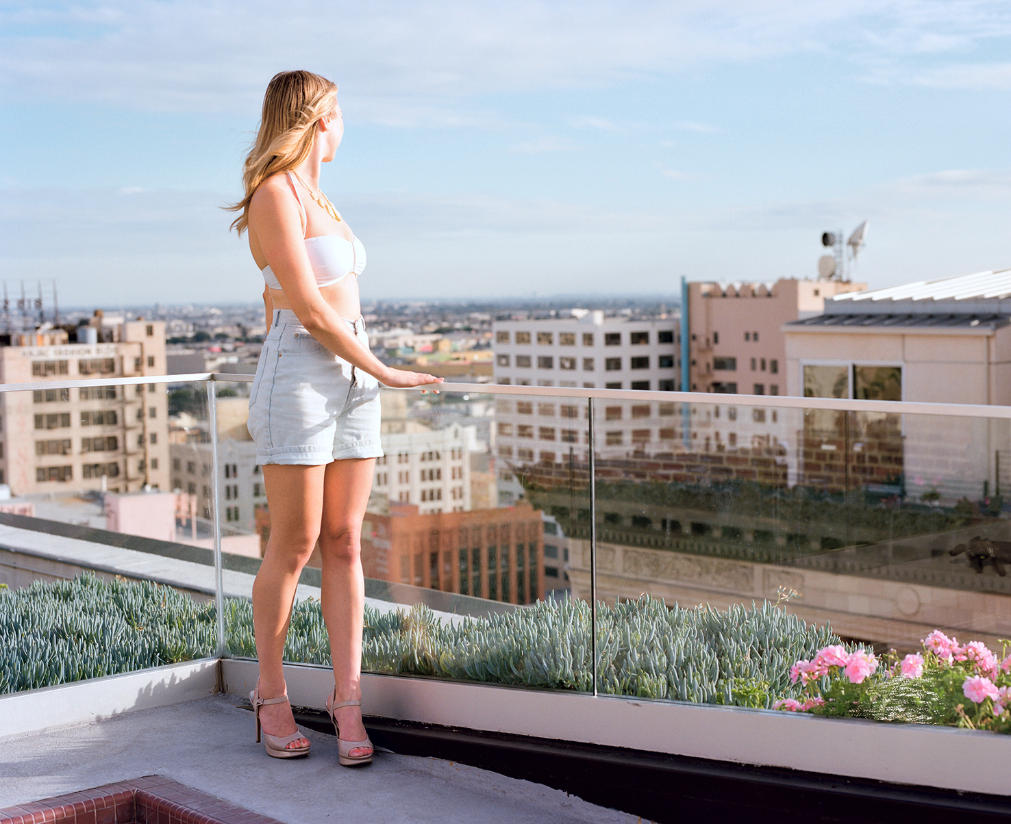 Full length portrait of blonde model Tasha Guida on a roof top looking away