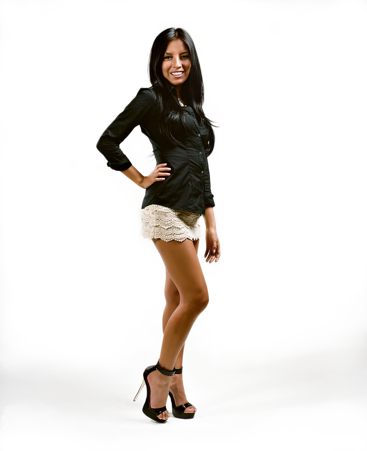 Full body studio portrait of Lissette with a hand on her right hip and arching her back