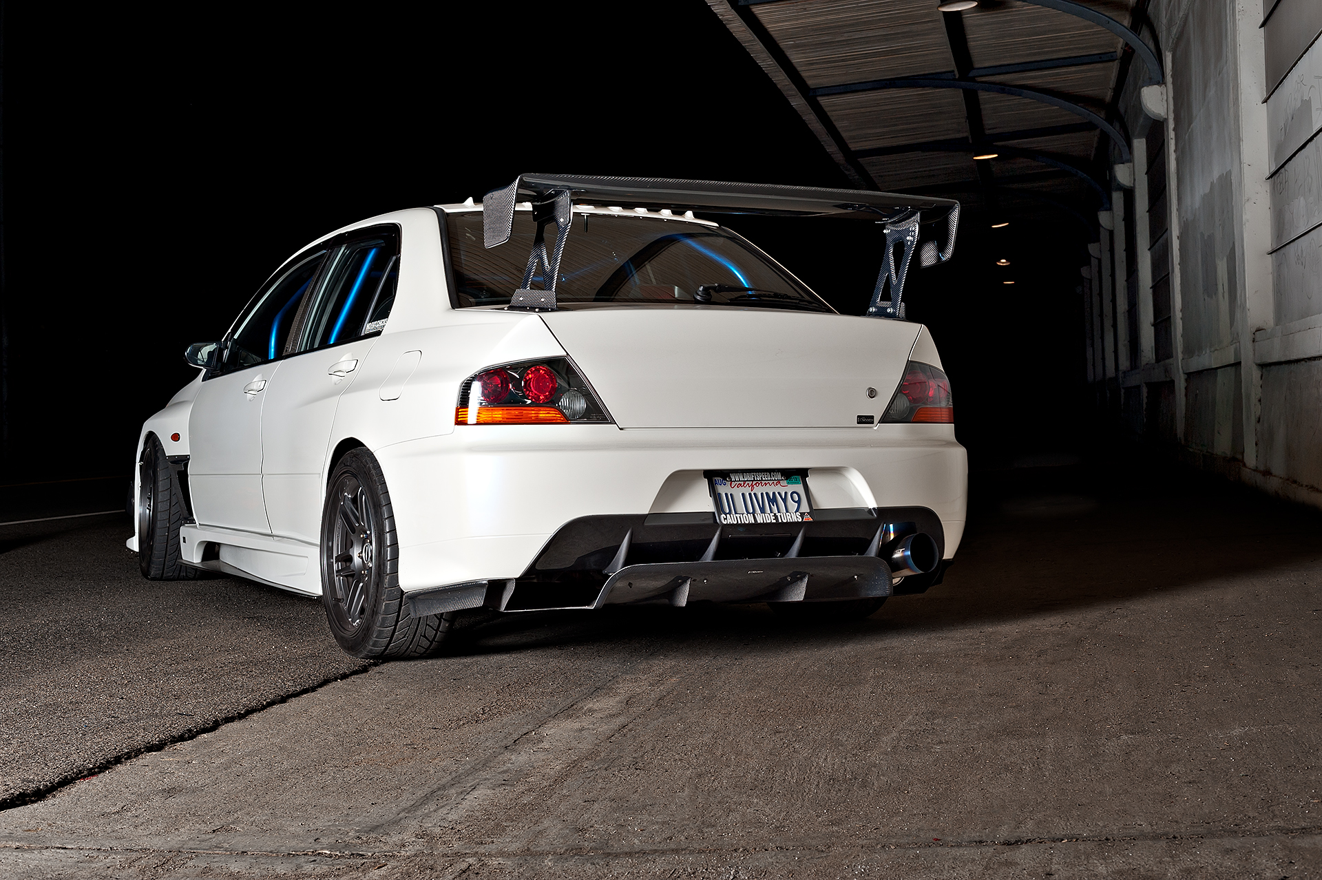 Rear 3/4 shot of White Mitsubishi Evo IX with Varis body kit