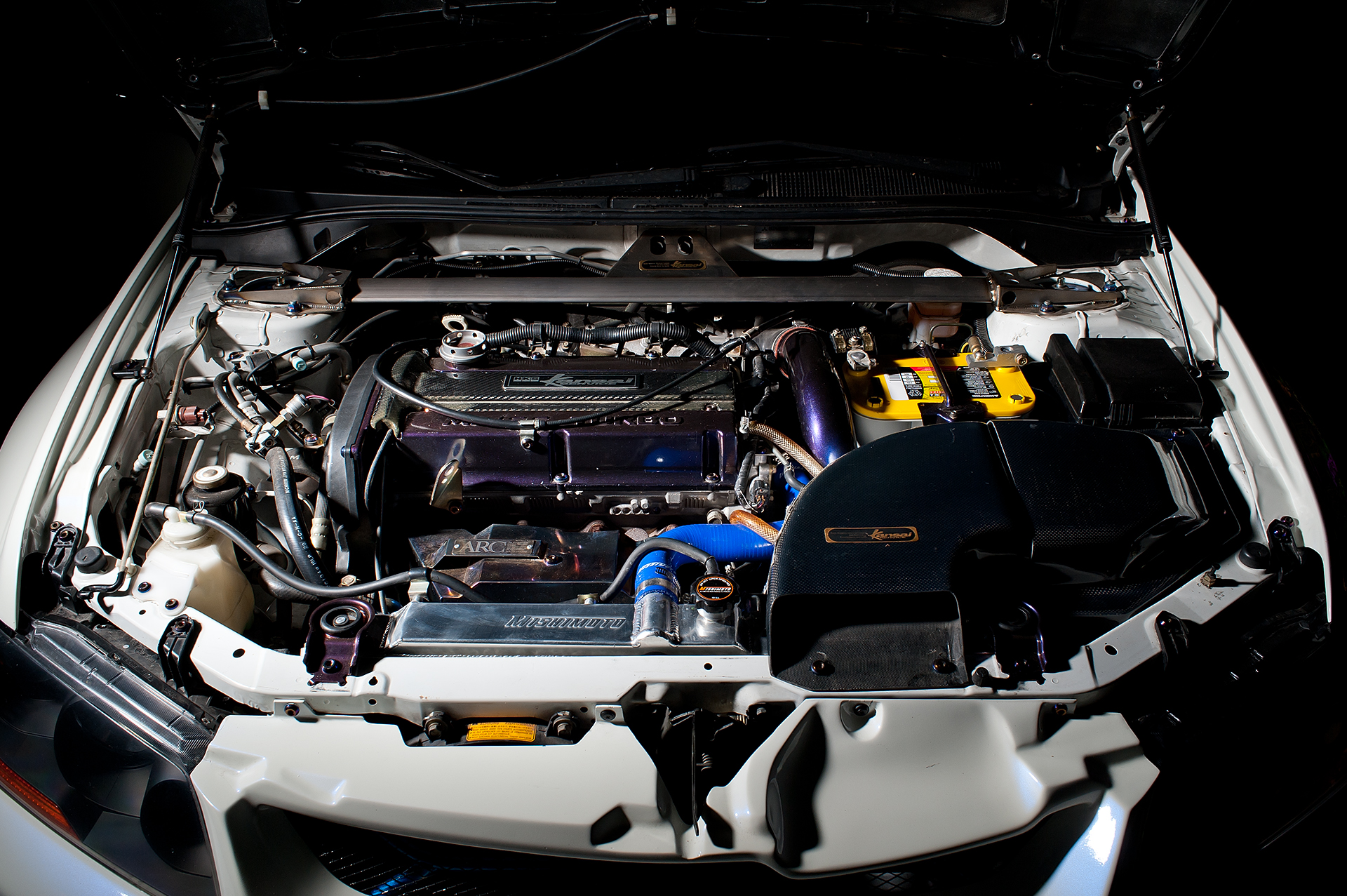 Engine bay shot of White Mitsubishi Evo IX with Varis body kit