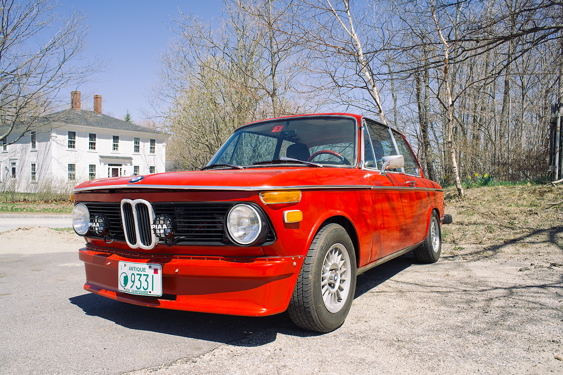Looking down the driver's side of a restored Red BMW 2002