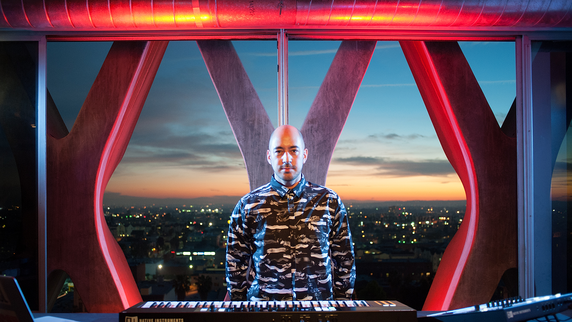 Mark de Clive-Lowe standing behind his keyboard and Maschine for the Native Instruments Komplete x Maschine shoot