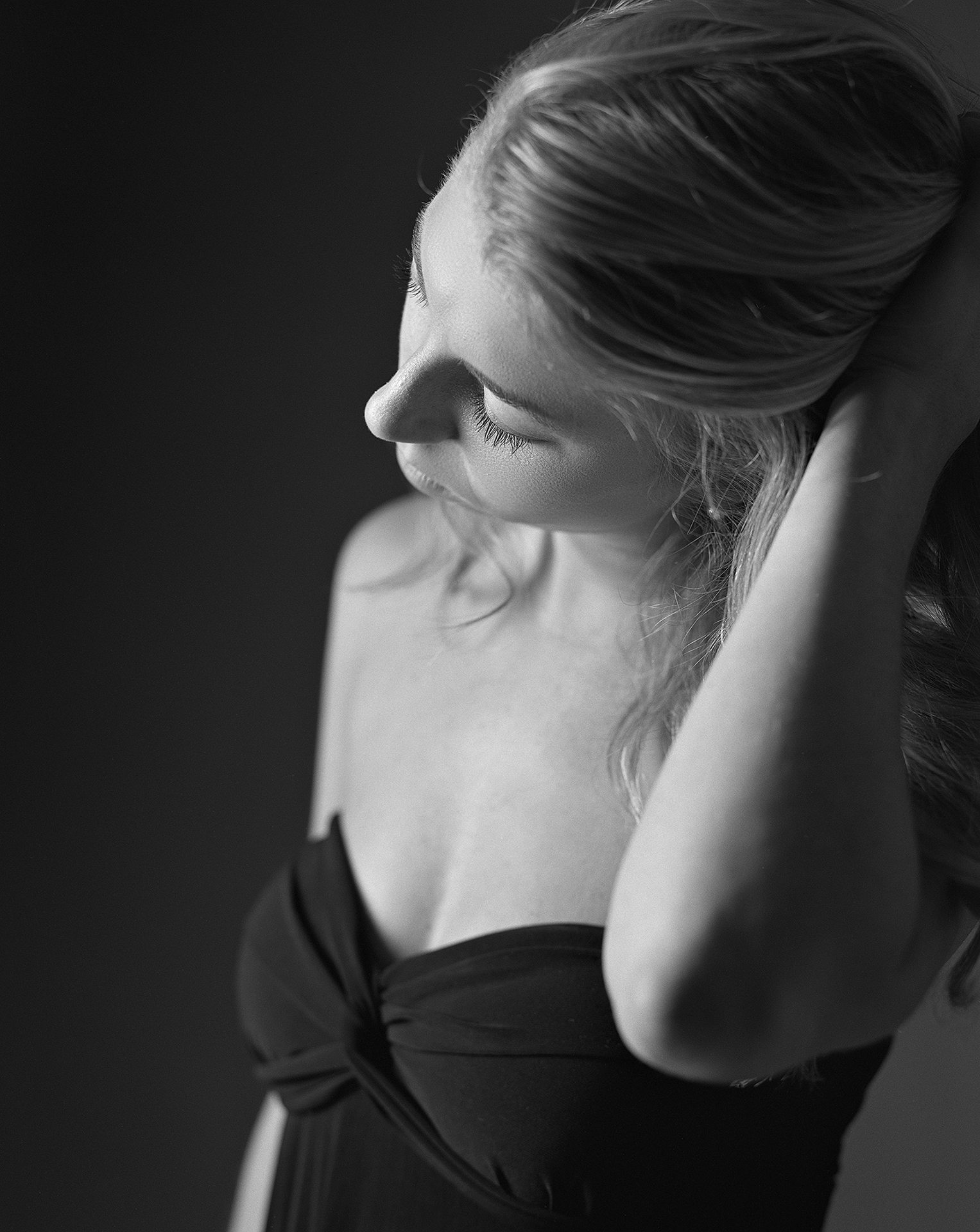 Black & white Tasha runs her hand through her hair for a portrait