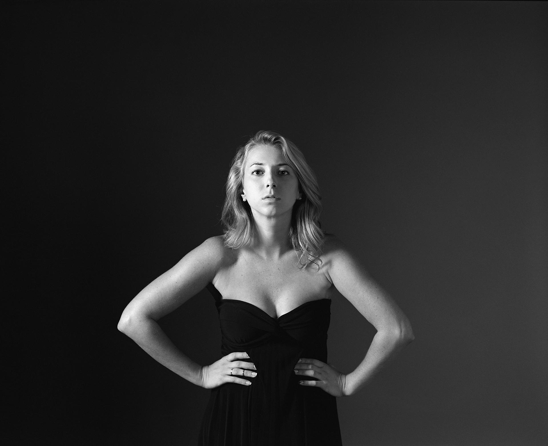 Black & white 1/2 length portrait of blonde model Tasha facing the camera head on in the studio